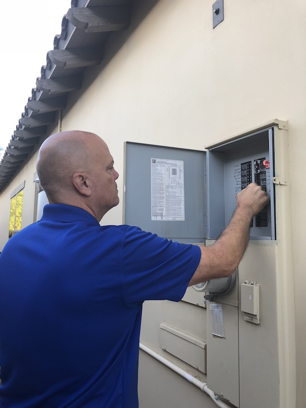Picture of Coachella Valley Home Watch owner Lou checking breaker panel